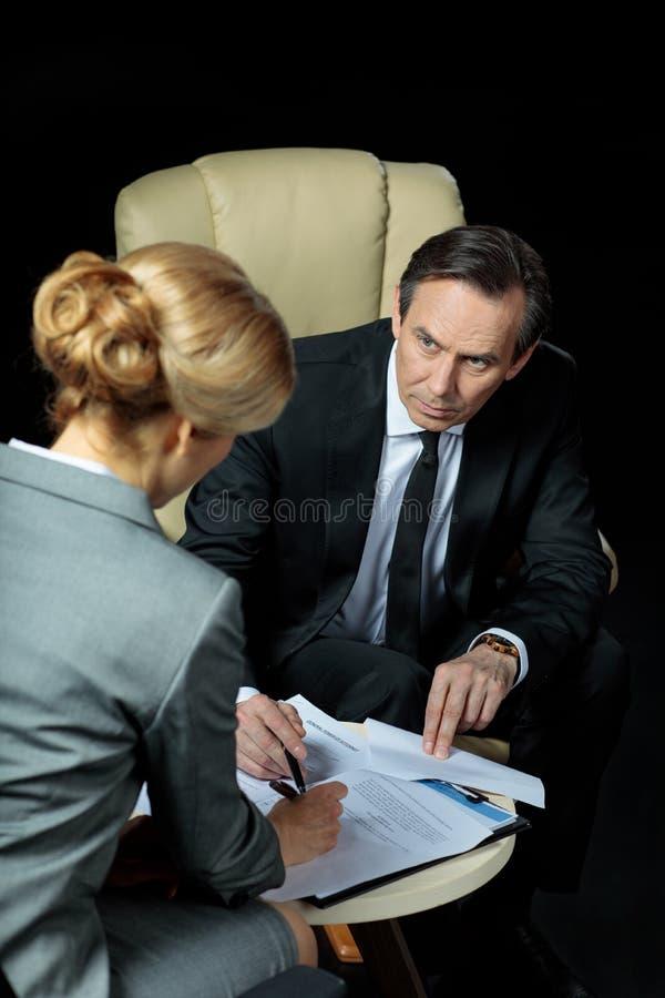 Reifer Geschäftsmann, der unterzeichnende Papiere der blonden Geschäftsfrau betrachtet lizenzfreies stockfoto