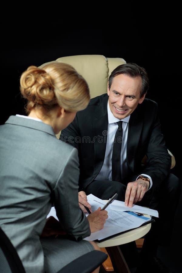 Reifer Geschäftsmann, der unterzeichnende Papiere der blonden Geschäftsfrau betrachtet stockfoto