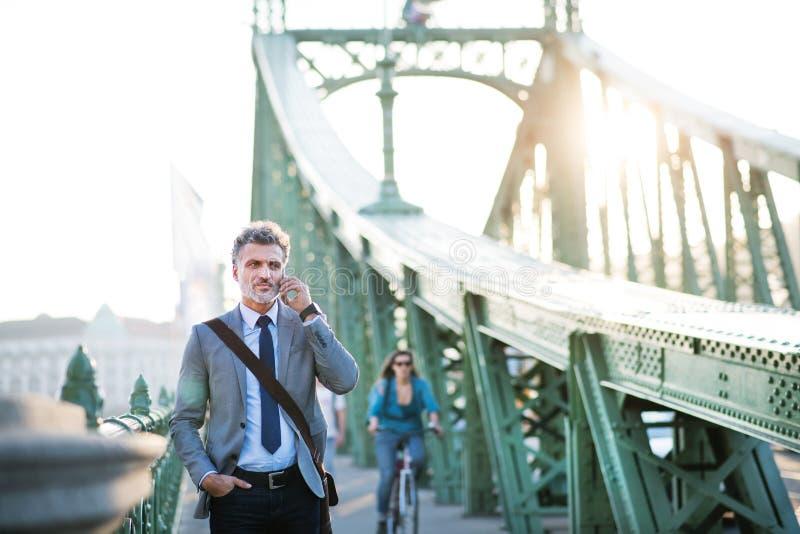Reifer Geschäftsmann mit einem Smartphone in einer Stadt lizenzfreie stockfotografie