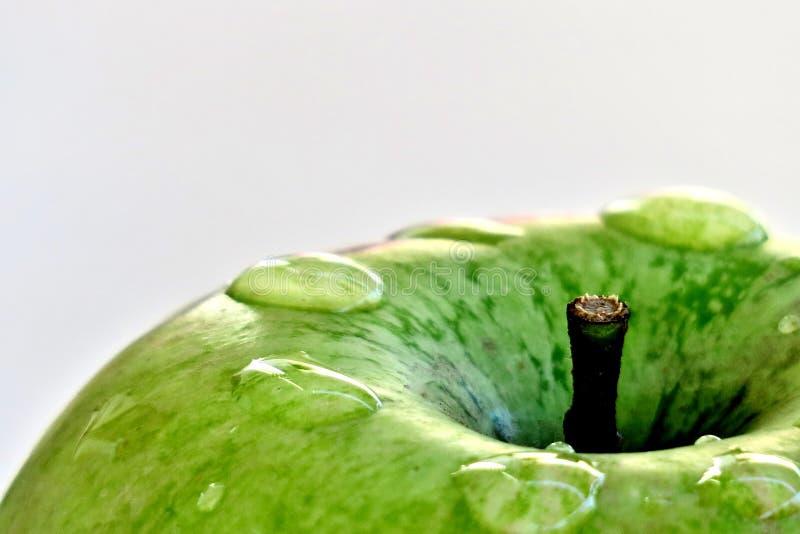 Reifer gr?ner Apfel auf einem wei?en Hintergrund mit Wassertropfen nach Regen lizenzfreies stockfoto