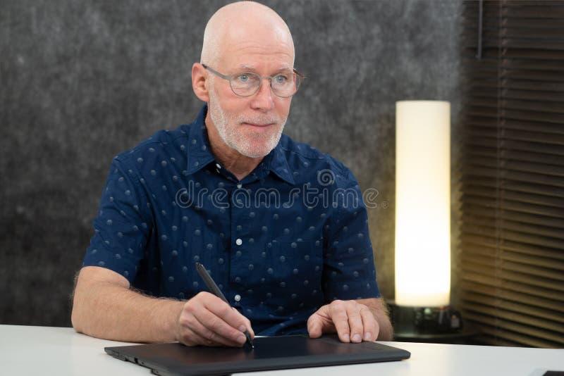 Reifer Grafikdesigner unter Verwendung des digitalisierten Stiftes stockfotos