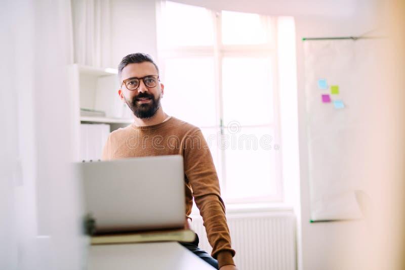 Reifer Hippie-Geschäftsmann mit Laptopfunktion in einem modernen Büro lizenzfreies stockbild