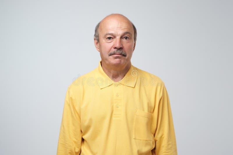 Reifer hispanischer Kerl des traurigen Umkippens im gelben Pullover, der mit Schuld und Traurigkeit schaut stockbild
