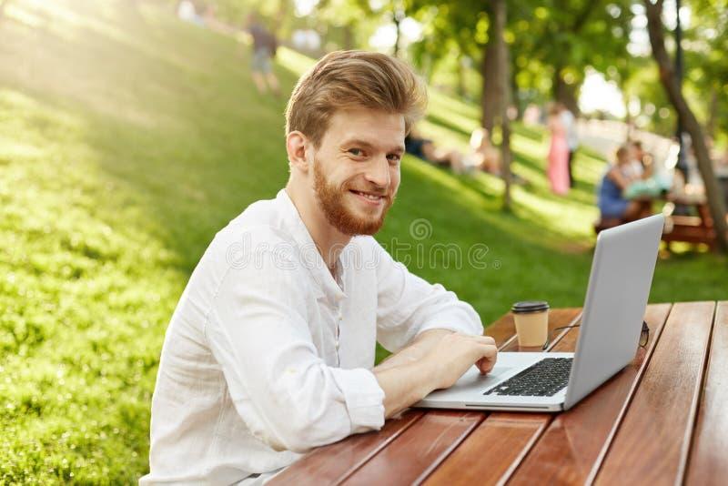 Reifer Ingwergutaussehender mann mit Bart in der zufälligen stilvollen Kleidung lächelt und sitzt im Park und betrachtet die Kame lizenzfreie stockfotos
