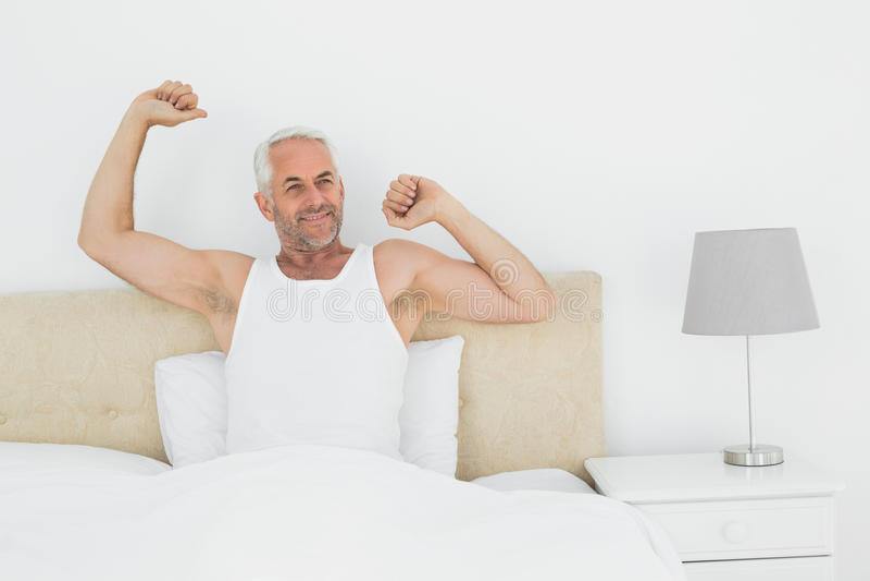 Reifer lächelnder Mann, der Arme im Bett ausdehnt stockbilder