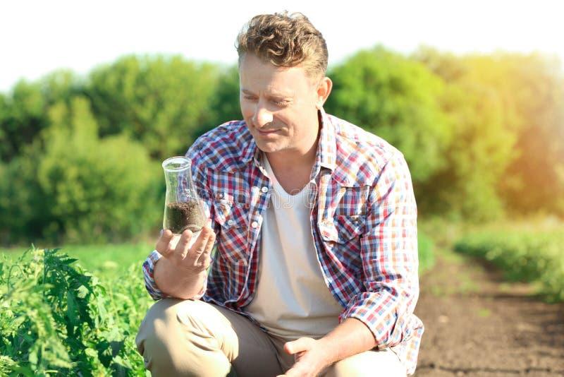 Reifer Landwirt, der Flasche mit Boden auf dem Gebiet hält lizenzfreies stockfoto