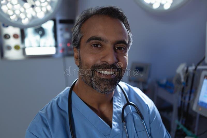 Reifer männlicher Chirurg, der Kamera bei der Stellung Raumes des in Kraft am Krankenhaus betrachtet lizenzfreie stockfotografie