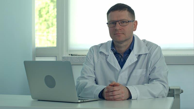 Reifer männlicher Doktor, der am Schreibtisch mit Laptop sitzt und Kamera in seinem Klinikbüro betrachtet lizenzfreies stockfoto