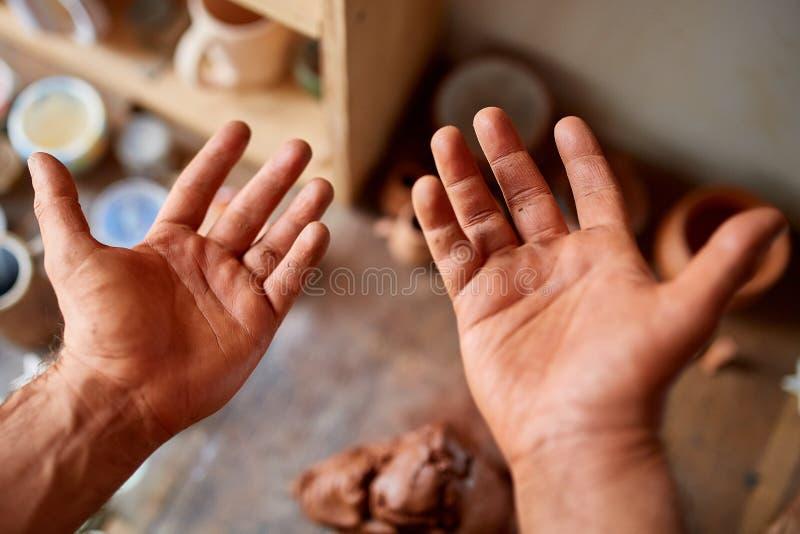 Reifer männlicher Töpfer, der seine Palmen bei der Gestaltung eines Lehms in der Tonwarenwerkstatt, Nahaufnahme, selektiver Fokus stockbilder