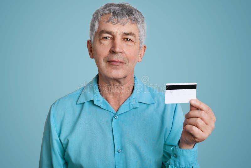 Reifer Mann Confidet mit dem grauen Haar, Griffplastikkarte, möchte Geld, gekleidetes iin stilvolles formales Hemd zurücknehmen,  lizenzfreies stockfoto