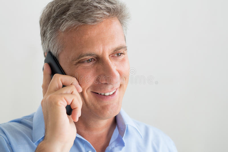 Reifer Mann, der auf Mobiltelefon spricht lizenzfreie stockfotografie