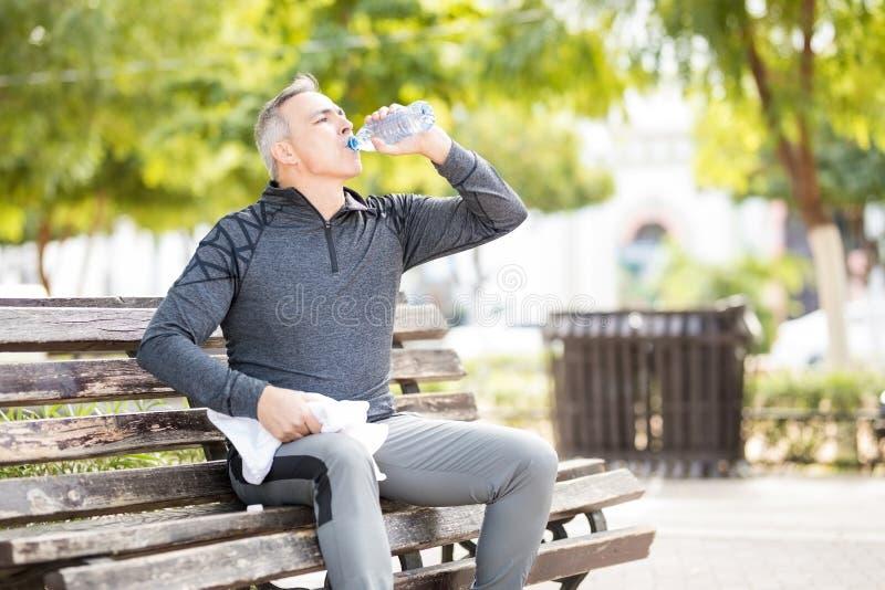 Reifer Mann, der Bruch und Trinkwasser nach Training nimmt stockbilder