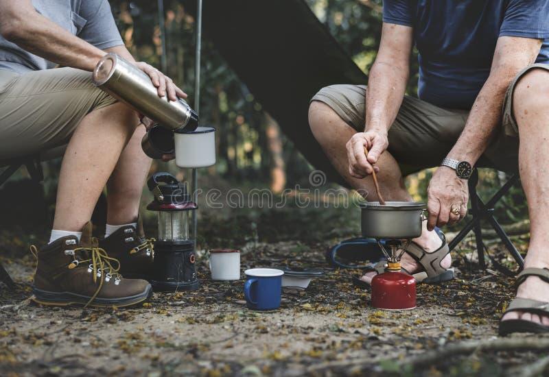 Reifer Mann, der an einem Campingplatz kocht stockbilder
