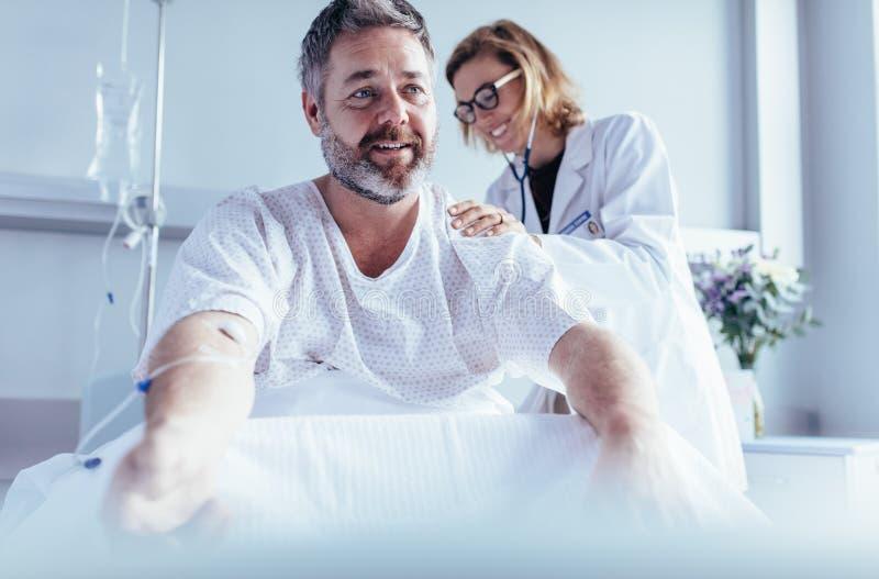 Reifer Mann, der im Krankenhausbett sitzen und Arzt, der Überprüfung tut stockbilder
