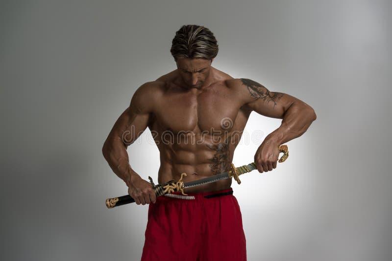 Reifer Mann, der Kriegers-Klinge hält stockfotos