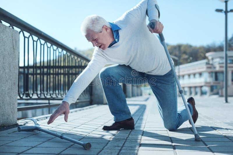 Reifer Mann, der seine Krücke erfasst, oben nachdem unten fallen stockbilder