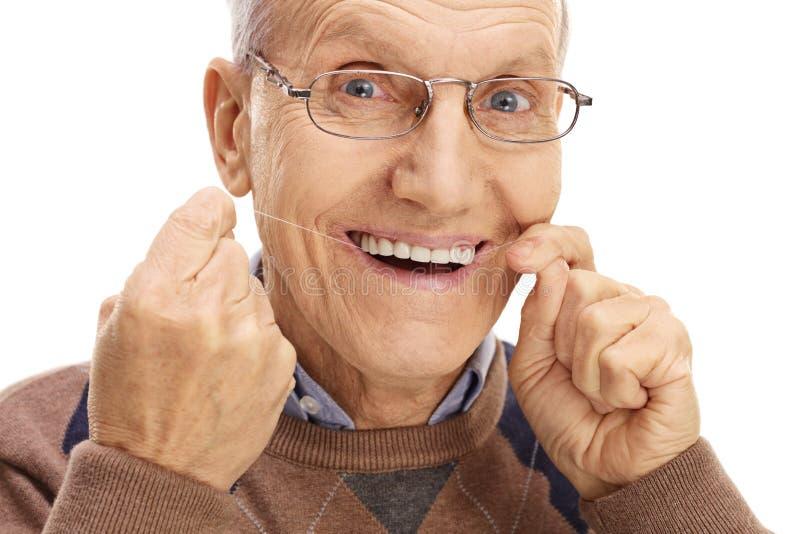 Reifer Mann, der seine Zähne flossing ist lizenzfreies stockfoto