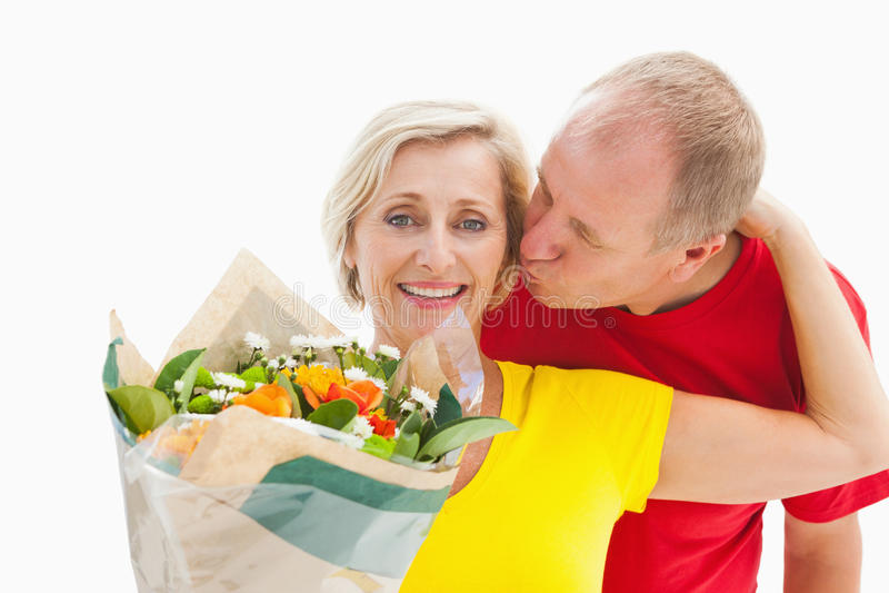 Reifer Mann, der seinen Partner hält Blumen küsst stockfotos