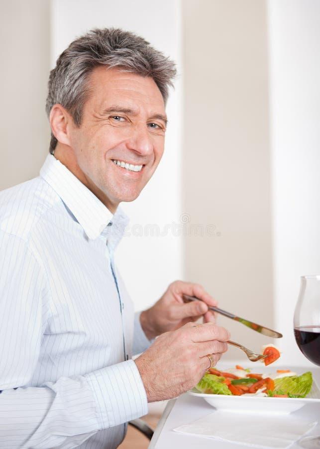 Reifer Mann, der zu Hause zu Mittag isst stockfotografie