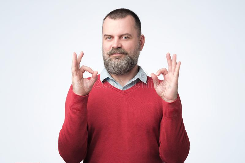 Reifer Mann im OKAYzeichen der roten Strickjackenvertretung lizenzfreie stockfotos