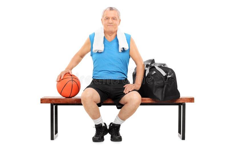 Reifer Mann mit dem Basketball, der auf einer Bank sitzt stockbild