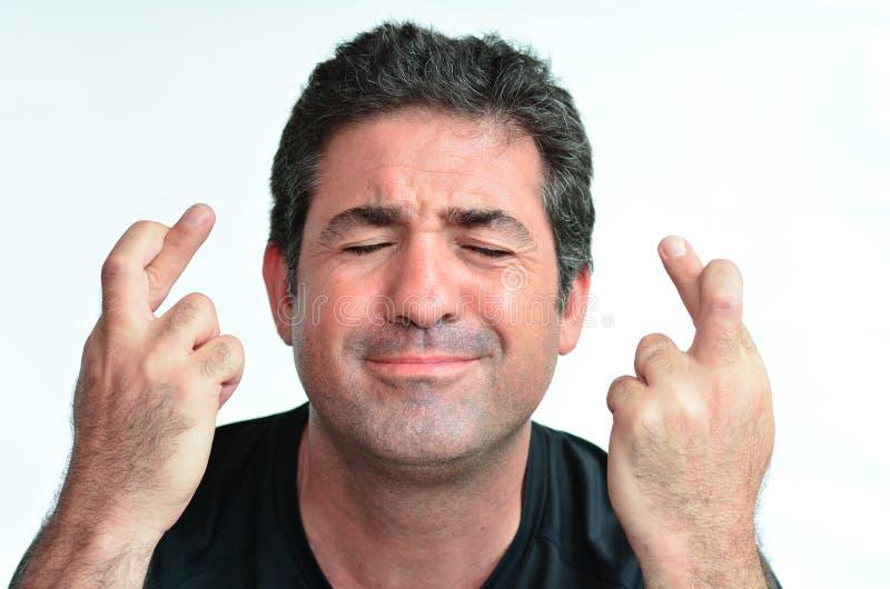 Reifer Mann mit den gekreuzten Fingern hoffend für Glück lizenzfreies stockfoto