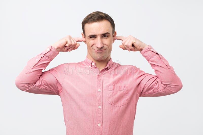 Reifer Mann mit den schließenden Ohren der Störung mit den Fingern, die nicht etwas hören wünschen stockfotos