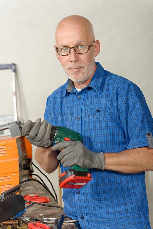 Reifer Mann mit einem Bohrgerät in seiner Werkstatt lizenzfreie stockfotografie