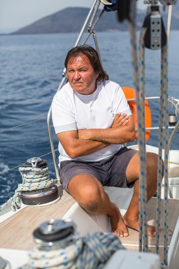 Reifer Mann sitzt auf seiner Segelyacht stockfoto