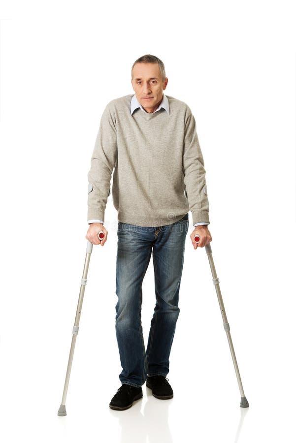 Reifer Mann in voller Länge mit Krücken lizenzfreies stockbild