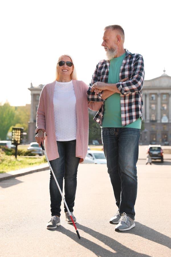 Reifer Mann, welche blinder Person mit dem langen Stockgehen hilft stockfoto