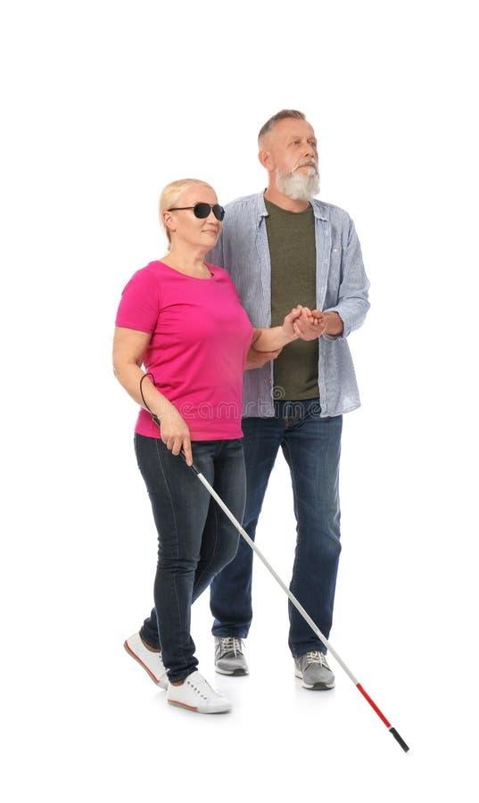 Reifer Mann, welche blinder Person mit langem Stock auf Weiß hilft stockbilder