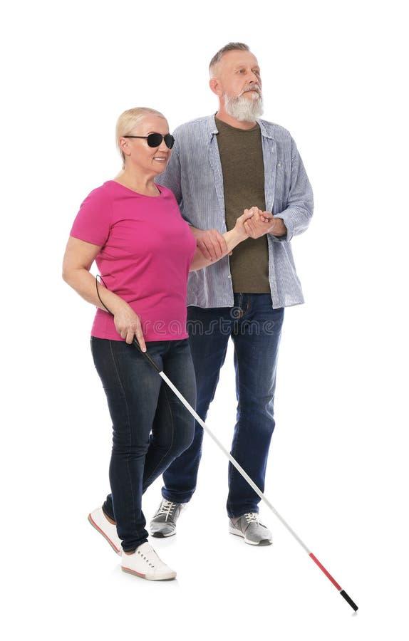 Reifer Mann, welche blinder Person mit langem Stock auf Weiß hilft stockfotos