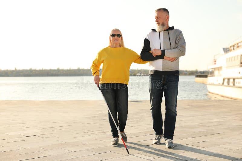 Reifer Mann, welche blinder Person mit langem Stock hilft lizenzfreie stockfotografie