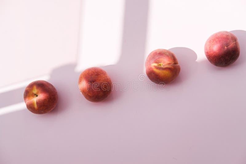 Reifer organischer Pfirsich auf rosa Hintergrund Flache Lage, Draufsicht lizenzfreies stockfoto