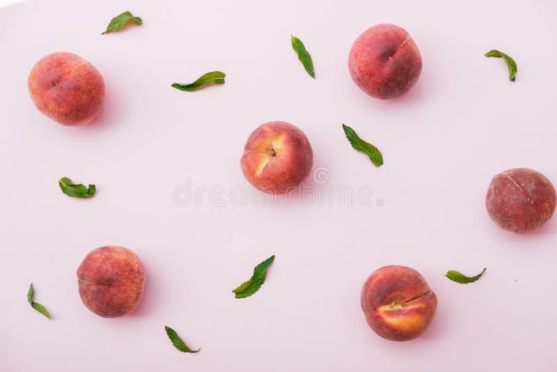 Reifer organischer Pfirsich auf rosa Hintergrund Flache Lage, Draufsicht lizenzfreie stockfotos