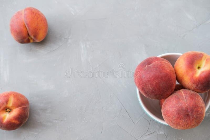 Reifer organischer Pfirsich in der blauen keramischen Schüssel im grauen Hintergrund oberseite lizenzfreie stockbilder