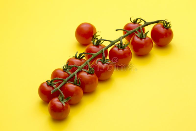 Reifer roter Cherry Tomatoes auf gelbem Hintergrund stockbild