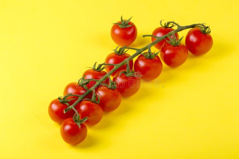 Reifer roter Cherry Tomatoes auf gelbem Hintergrund lizenzfreies stockbild