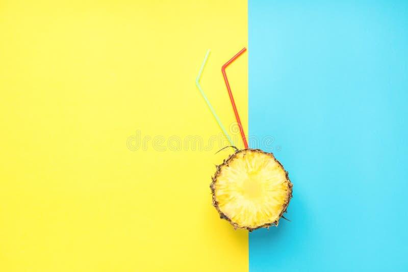 Reifer saftiger Schnitt in der halben Ananas mit rotem und grünem gelbem blauem Hintergrund Trinkhalme Duotone Frische Saft-Somme stockfotografie
