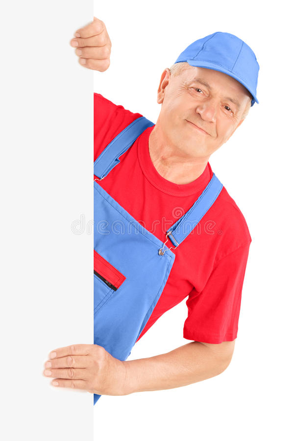 Reifer Schlosser, der hinter einer Leerplatte lächelt und aufwirft stockfotos