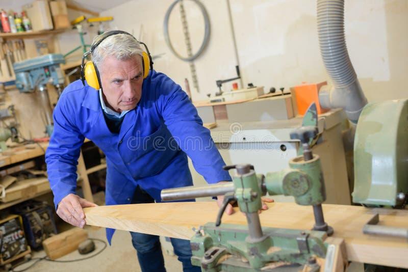 Reifer Tischler, der an der Werkstatt arbeitet stockbild