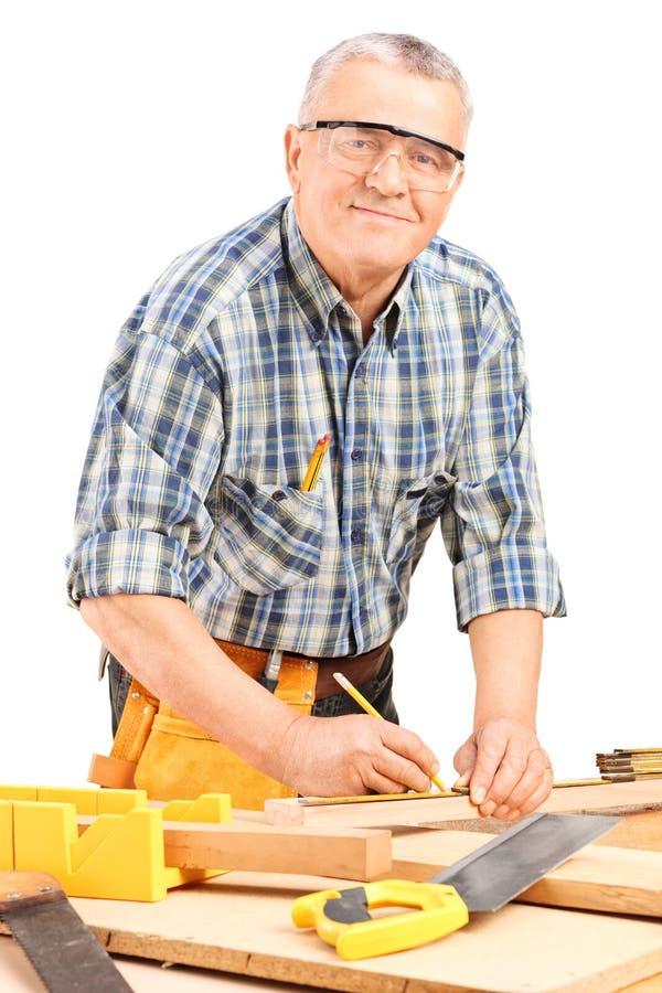 Reifer Tischler, der eine Planke misst stockfotos