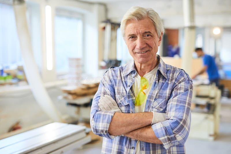 Reifer Tischler in der Werkstatt stockbild