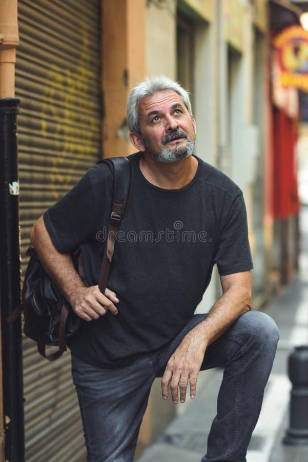 Reifer touristischer Mann mit Reiserucksack im städtischen Hintergrund lizenzfreie stockfotos
