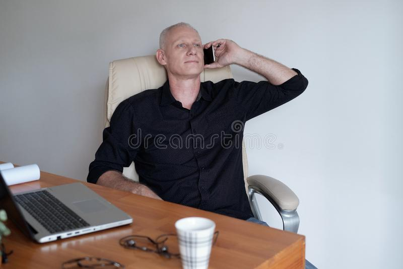 Reifer Unternehmer Talking On Phone stockfotografie