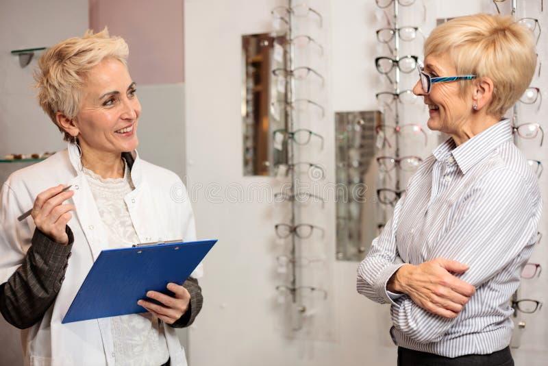 Reifer weiblicher Augenarzt, der die Daten des Patienten zu einem Klemmbrett, arbeitend in einen optischen Speicher schreibt stockbild
