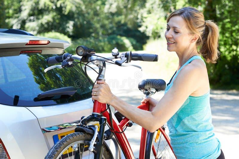 Reifer weiblicher Radfahrer, der Mountainbike vom Gestell auf Auto nimmt lizenzfreies stockfoto