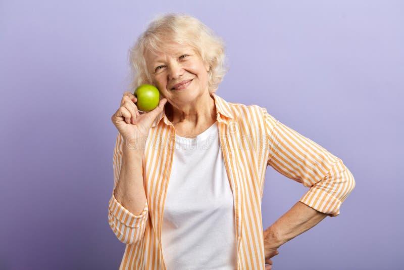 Reifes Alter und gesunde Ern?hrung ?lteres Frauenl?cheln, einen gr?nen Apfel halten lizenzfreie stockbilder