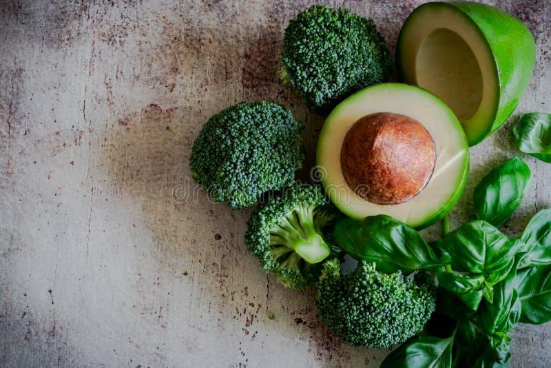 Reifes Gemüse und Früchte: Brokkoliblütenstände, Avocado und wohlriechender Basilikum auf einem schönen Hintergrund stockfotografie
